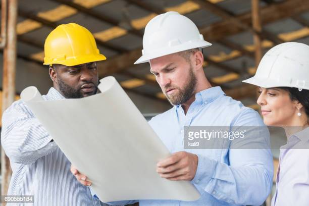 Multi-ethnic workers in hardhats looking at plans