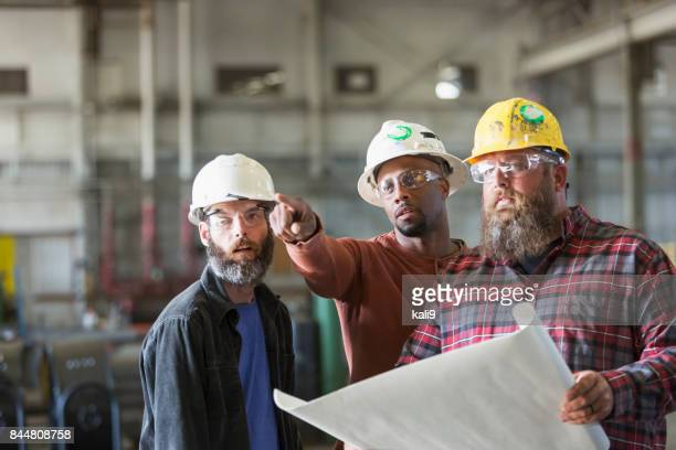 Multi-ethnic workers in hardhats with plans