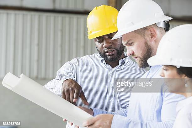 Multi-ethnic workers wearing hardhats looking at plans
