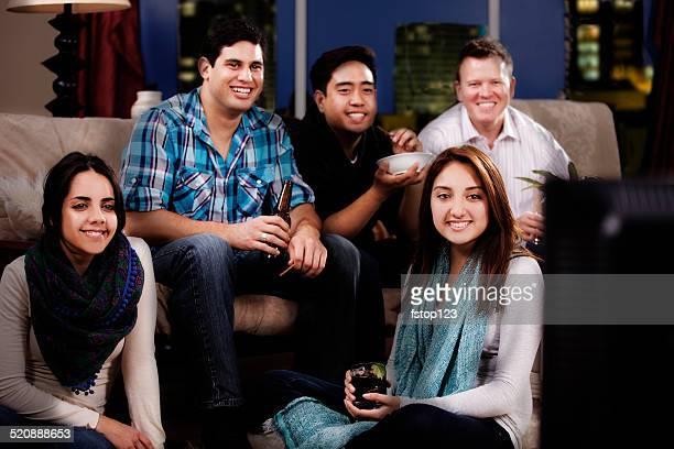 Multi-ethnique jeune adulte amis traîner appartement, du centre-ville. Regarder la télévision.