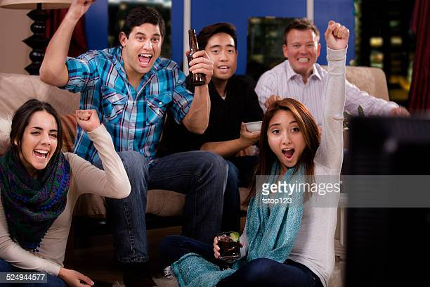 Multi-ethnic young adult friends hanging out, downtown apartment. Watch TV.