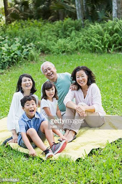 Multi-generation Asian family sitting together outdoors