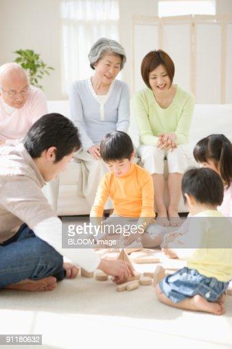 Multi-generation family, children playing with blocks : Stock Photo