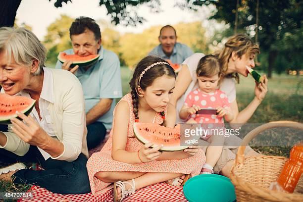 Multi-generation Family Eating Watermelon At Picnic.