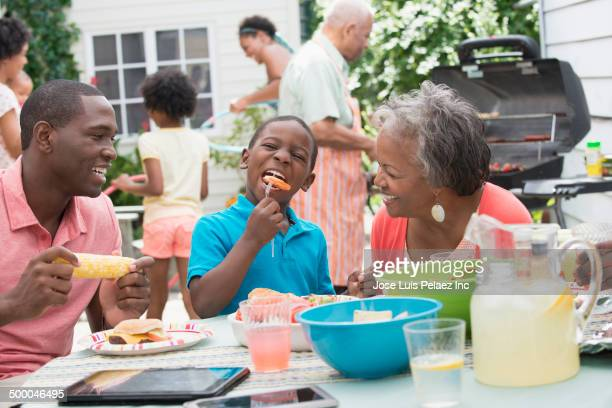 Multi-generation family enjoying backyard barbecue