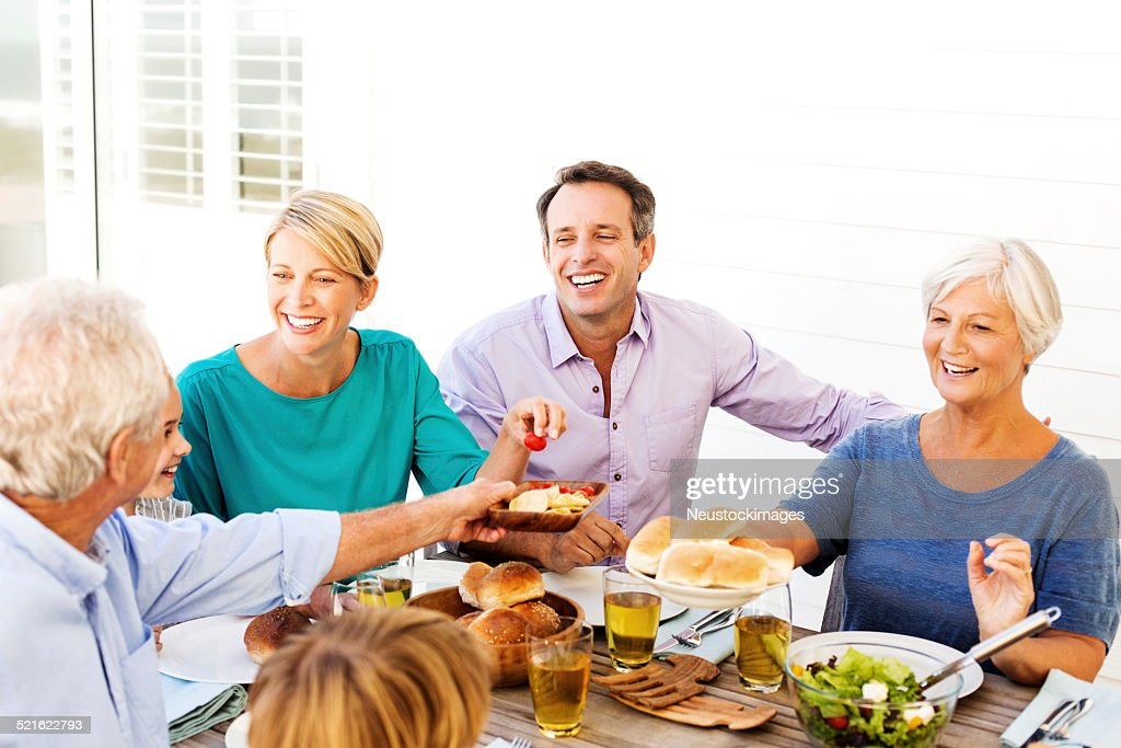 Multi-Generation Family Enjoying Meal At Table On Patio : Stock Photo