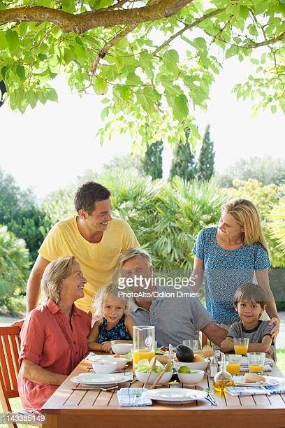 Multi-generation family having breakfast outdoors