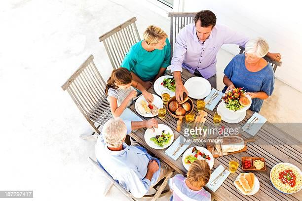 Familia Multi-generacional tener comida en la mesa en el porche