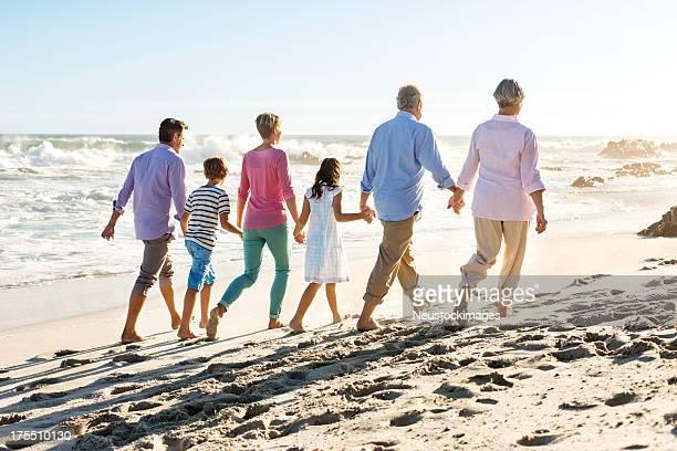 Família de várias gerações de mãos dadas enquanto a caminhar pela praia