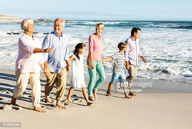 Multi-Generationen-Familie Hände halten, zu Fuß am Strand