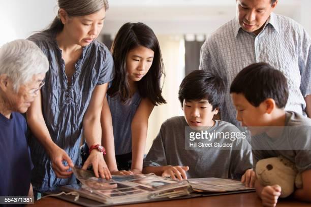 Multi-generation family looking at photo album