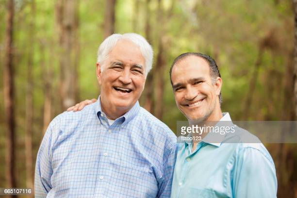 Multi-generation family of father and son hugging outdoors together.