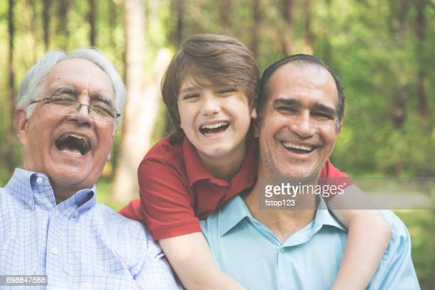Multi-generation family of grandfather, grandson, father hugging outdoors together.