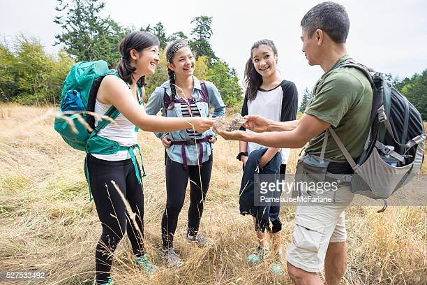 Multi-Generation Family of Hikers Examining Wasp Nest in Grassy Field
