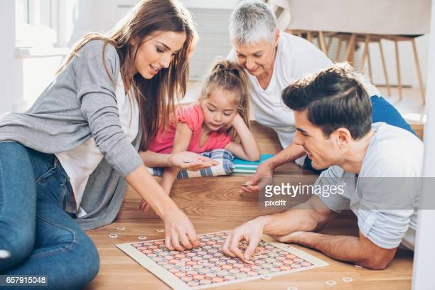 Multi-generation family playing a board game