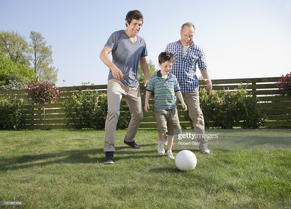 Multi-generation family playing soccer in backyard : Stock Photo