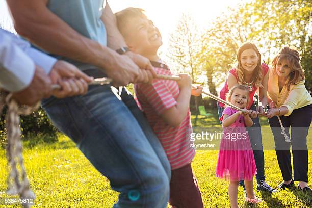 Multi-generation family playing tug of war in nature.