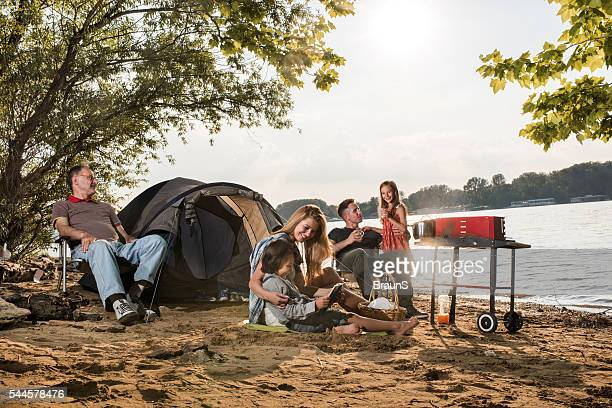 Multi-generation family relaxing on a camping by the river.