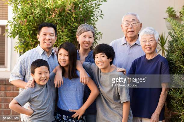 Multi-generation family smiling outdoors