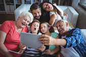 Multi-generation family taking a selfie on digital tablet in living room at home