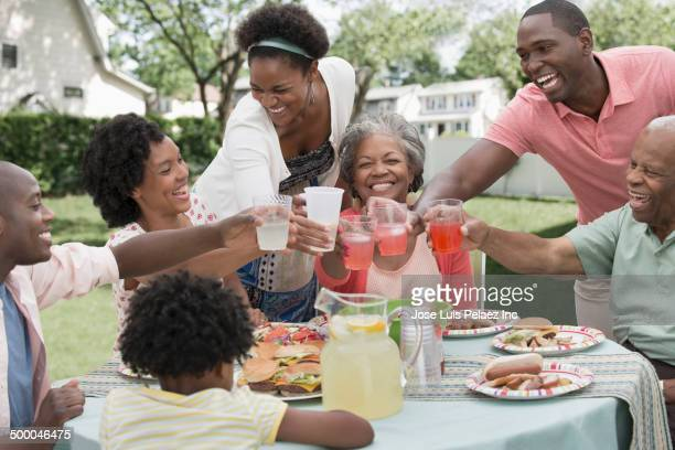 Multi-generation family toasting glasses at barbecue