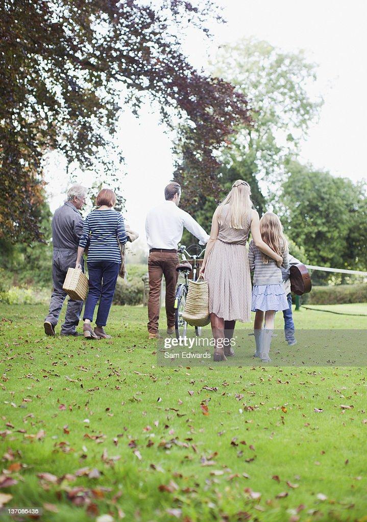 Multi-generation family walking in park : Stock Photo