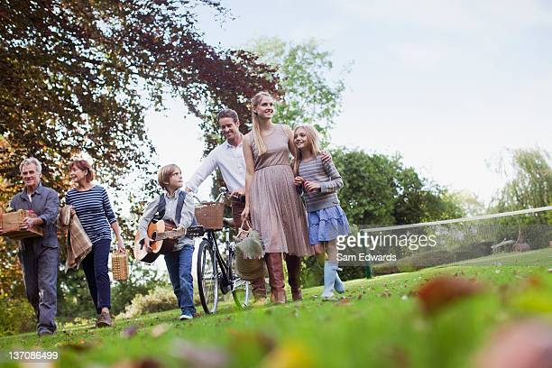Multi-generation family with picnic baskets walking in park