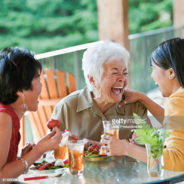 Multi-generation Japanese women eating and laughing