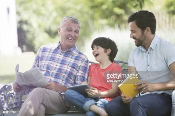 Multi-generation men laughing on bench