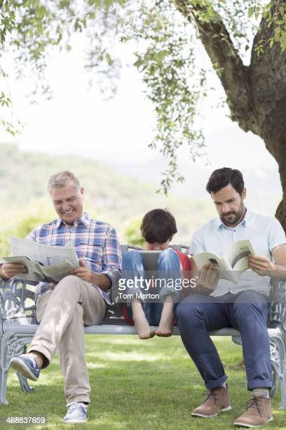 Multi-generation men reading on bench