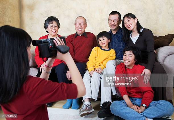 Multi-generational Asian family being video recorded