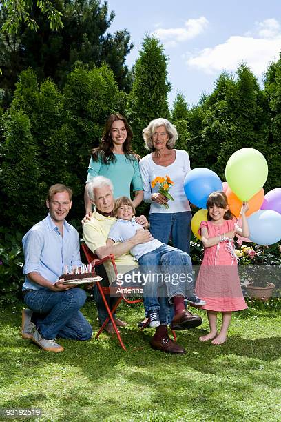 A multi-generational family celebrating a birthday, outdoors