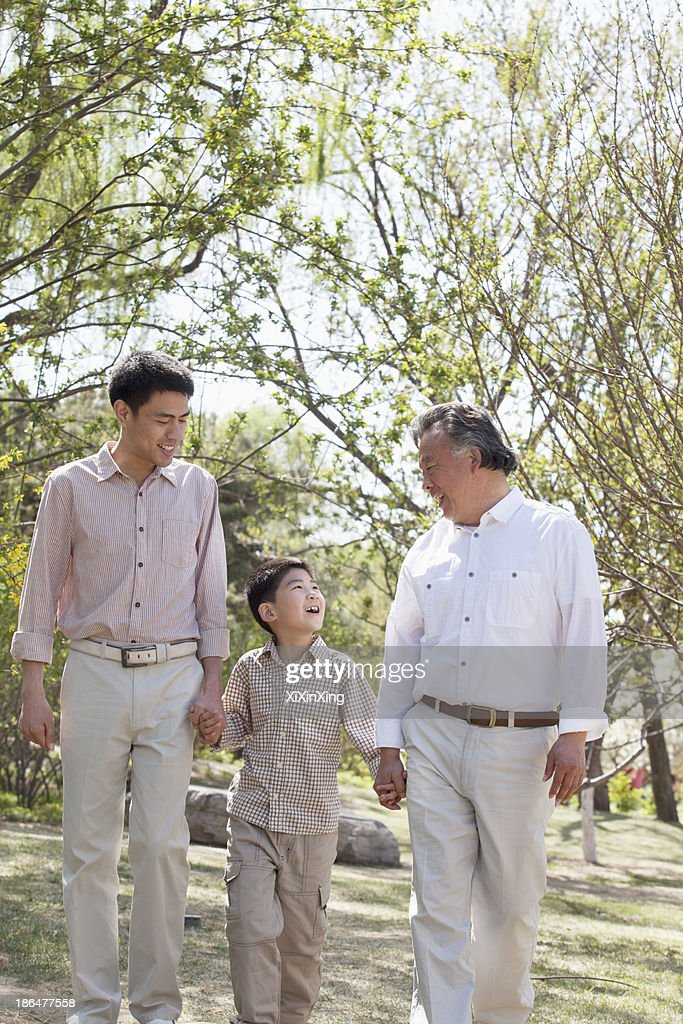 Multi-generational family, grandfather, father, and son holding hands and going for a walk in the park in springtime : Stock Photo