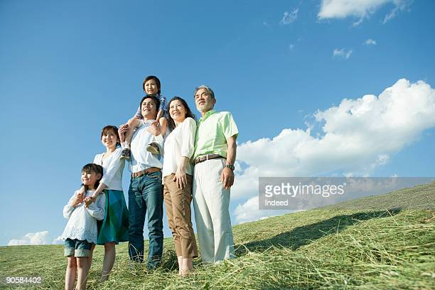 Multi-generational family in grass field