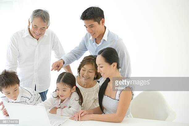Multigenerational family looking at laptop monitor