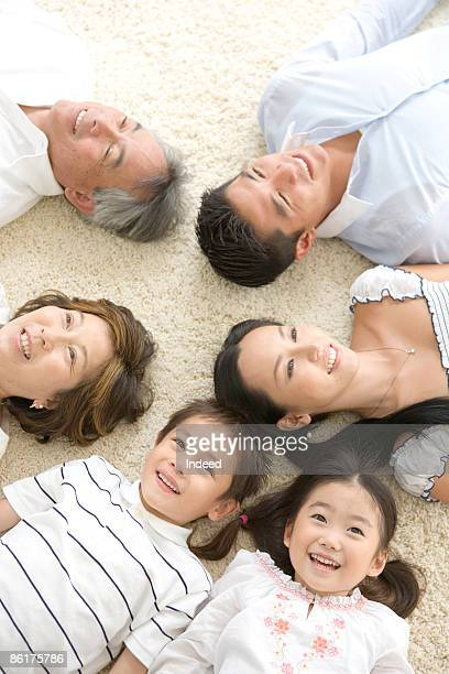 Multigenerational family lying on back, smiling