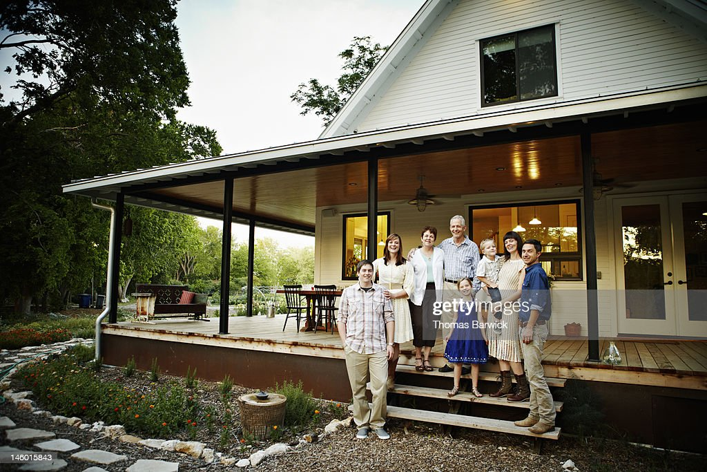 Multigenerational family outside on porch of home : Stock Photo