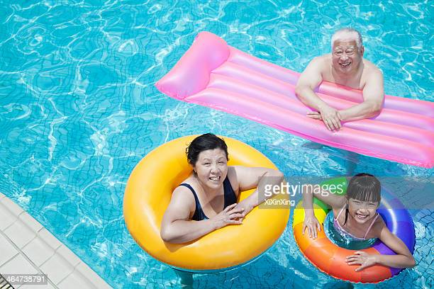Multi-generational family playing in the pool with inflatable tubes, looking at camera