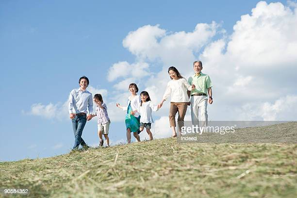 Multi-generational family playing on field