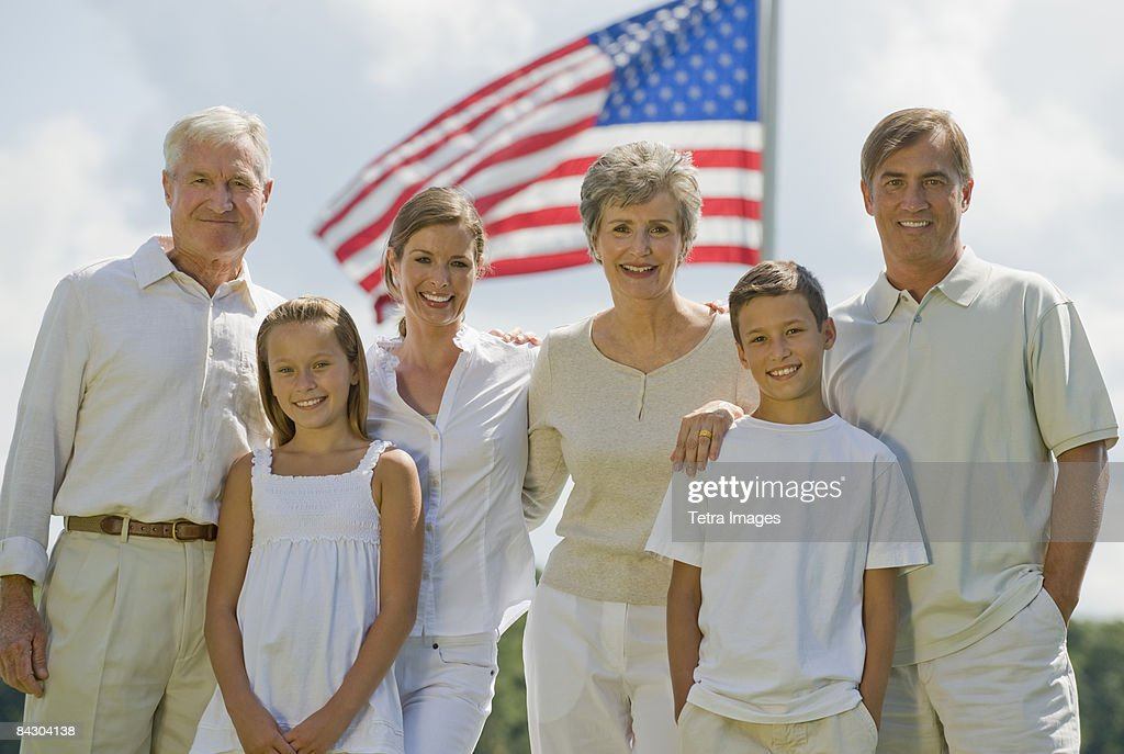Multi-generational family posing in front of American flag : Stock Photo