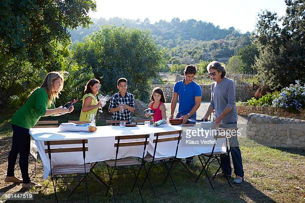 Multigenerational family preparing dining table