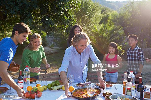 Multigenerational family setting dinner table
