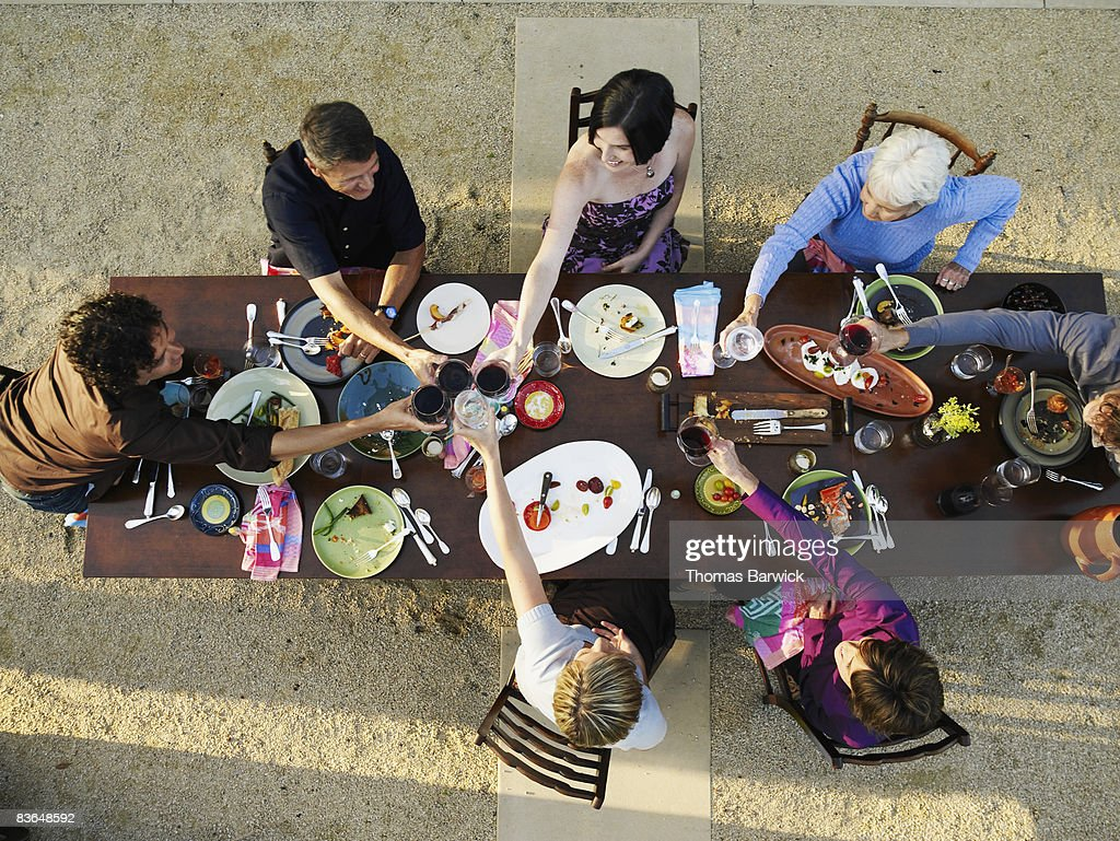 Multigenerational family toasting at outdoor table : Stock Photo