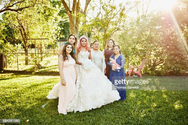 Multigenerational female family members posing for quinceanera photos in backyard