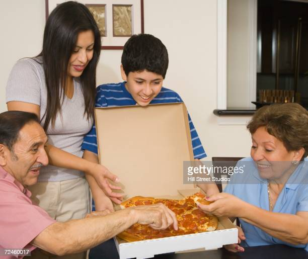 Multi-generational Hispanic family eating pizza