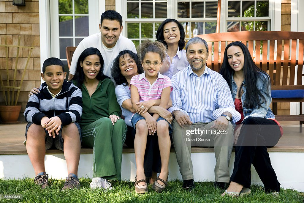 Multigenerational Hispanic family on porch : Stock Photo