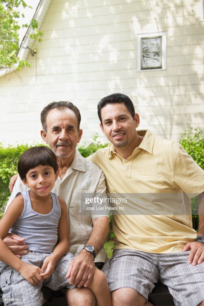 Multi-generational Hispanic family sitting outdoors : Stock Photo