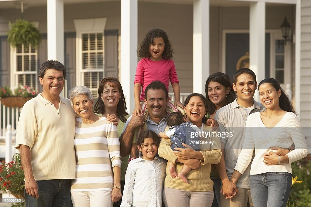 multigenerational hispanic family smiling in front of