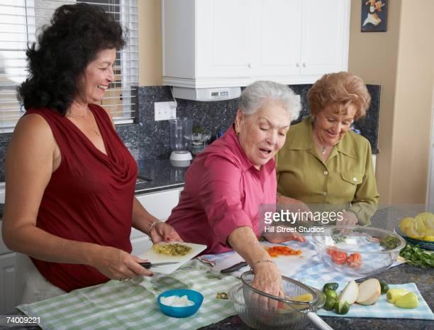 Multi-generational Hispanic female family members preparing food