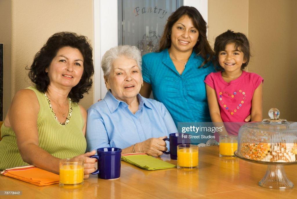 Multi-generational Hispanic female family members smiling at breakfast table : Stock Photo